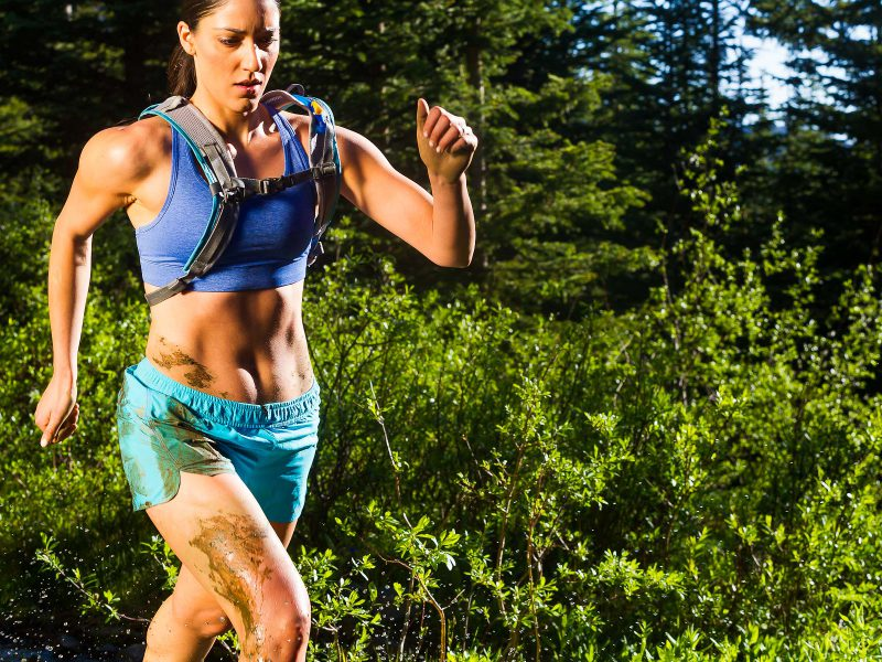athlete, fitness, training, young woman, Hispanic, hard charging, muddy, sweaty, running, focused, muscular, green, summer, Sangre de Cristo Mountains, Taos Ski Valley, New Mexico